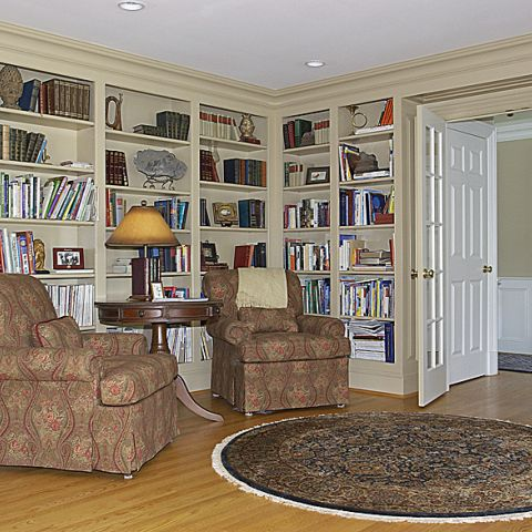 Small library with wood built-ins and comfortable settees