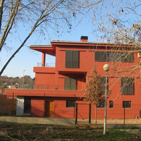 back exterior of red urban villa - Ballard & Mensua